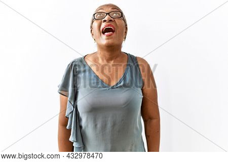 Mature hispanic woman wearing glasses standing over isolated background angry and mad screaming frustrated and furious, shouting with anger. rage and aggressive concept.