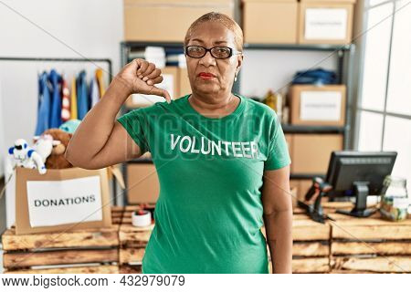 Mature hispanic woman wearing volunteer t shirt at donations stand with angry face, negative sign showing dislike with thumbs down, rejection concept