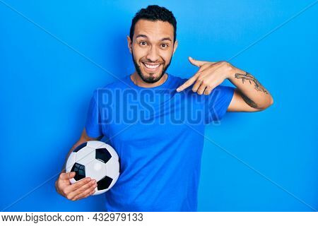 Hispanic man with beard holding soccer ball looking confident with smile on face, pointing oneself with fingers proud and happy.