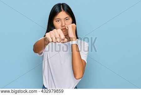 Beautiful young asian woman wearing casual white t shirt punching fist to fight, aggressive and angry attack, threat and violence