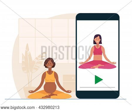 Online Yoga. Pregnant African American Woman Sitting In Lotus Position On Mat At Home. Woman Watches