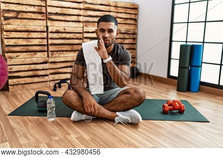 Young indian man sitting on training mat at the gym hand on mouth telling secret rumor, whispering malicious talk conversation
