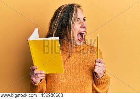 Young blonde woman holding book and pencil angry and mad screaming frustrated and furious, shouting with anger. rage and aggressive concept.
