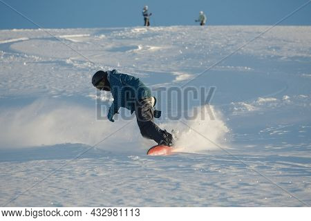 LES ORRES, FRANCE - JANUARY 23, 2015: Young snowboarder coming down fast in fresh powder snow off-piste free ride.