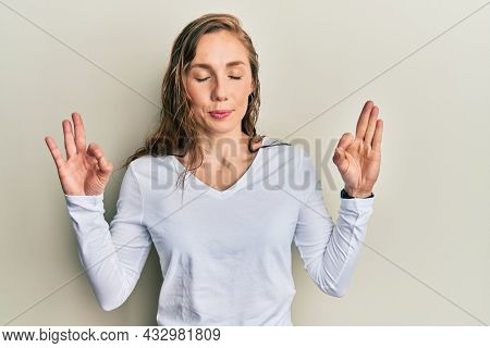Young blonde woman wearing casual clothes relax and smiling with eyes closed doing meditation gesture with fingers. yoga concept.
