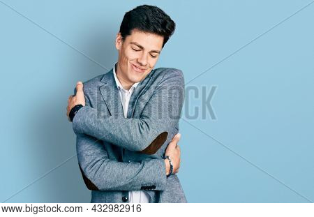 Young hispanic man wearing business clothes hugging oneself happy and positive, smiling confident. self love and self care