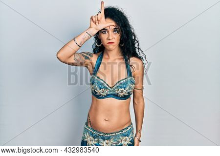 Young woman wearing bindi and traditional belly dance clothes making fun of people with fingers on forehead doing loser gesture mocking and insulting.