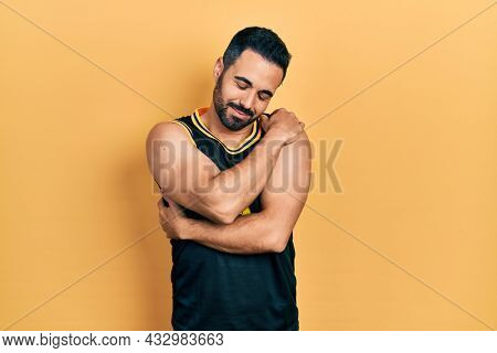Handsome hispanic man with beard wearing basketball t shirt hugging oneself happy and positive, smiling confident. self love and self care