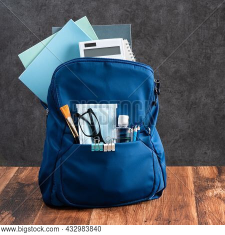 Close Up Of Blue Backpack With School Stationery Over Wooden Table And Black Background, Back To Sch