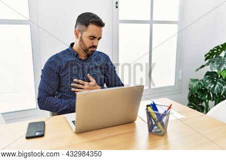 Young hispanic man with beard working at the office with laptop with hand on stomach because indigestion, painful illness feeling unwell. ache concept.