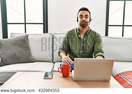 Young hispanic man with beard wearing call center agent headset working from home puffing cheeks with funny face. mouth inflated with air, crazy expression.