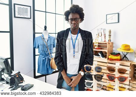African young woman working as manager at retail boutique depressed and worry for distress, crying angry and afraid. sad expression.