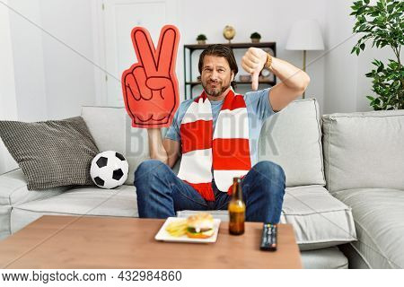 Handsome middle age man football hooligan cheering game at home with angry face, negative sign showing dislike with thumbs down, rejection concept