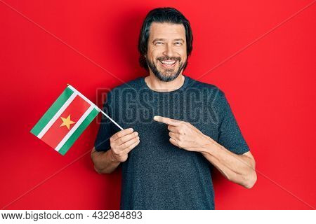 Middle age caucasian man holding suriname flag smiling happy pointing with hand and finger