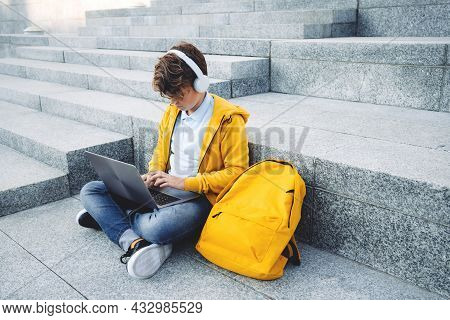 Child Boy With Headphones Studying At Home With Laptop