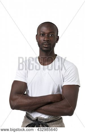 African waiter with a white T-shirt and crossed arms poses on white background. Studio portrait. Copy-space