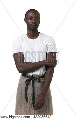 African boy with apron poses frontal on white background in photo studio. Half-length portrait. Copy-space