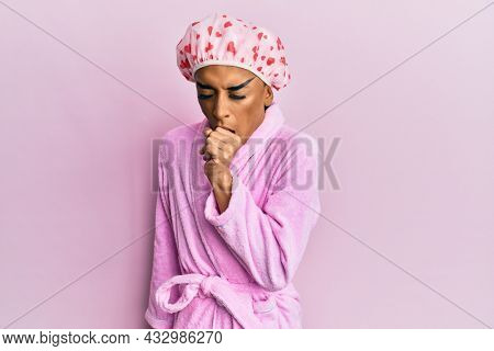 Hispanic man wearing make up wearing shower towel cap and bathrobe feeling unwell and coughing as symptom for cold or bronchitis. health care concept.