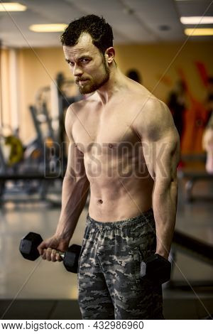 A Young Man Of Athletic Physique Is Engaged With Dumbbells In The Gym.