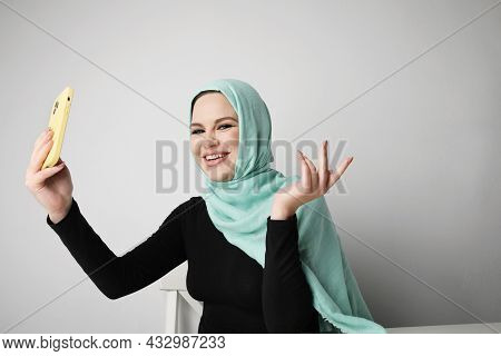 Arabian Woman With Happy Smile Using Smartphone, Posing On White Wall.