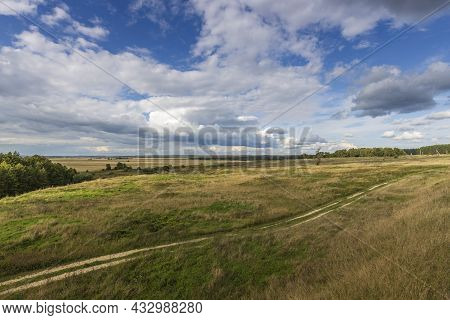 Landscape With Trees On A Hill Against A Blue Sky With Clouds. The Road To The Top Of The Hill. Brig