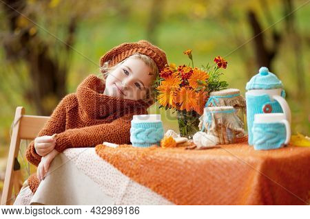 Adorable Little Girl On Picnic In Autumn Park. Cute Little Girl  Having Tea Party Outside In The Aut