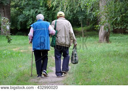 Elderly Couple Walking In A Park Holding Hands. Old Man Holds Woman With Cane By The Arm, Life In Re