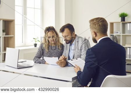 Young Couple Reading Some Documents Sitting At Desk In Real Estate Agents Office