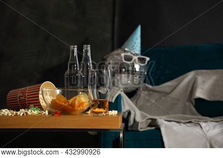 Messy Table With Food Leftovers Near Clothes On Armchair In Room After Party