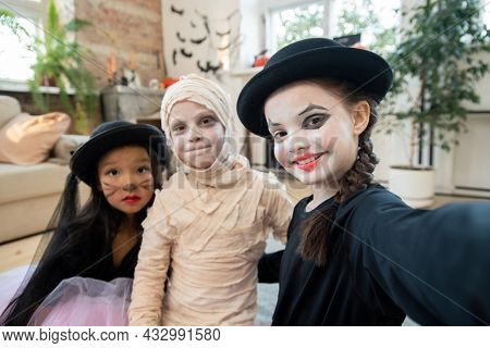 Happy halloween girl in black attire making selfie with two kids in costumes