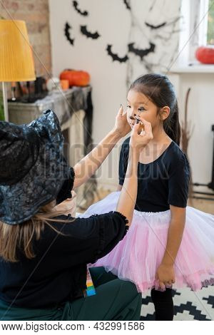 Young woman in black halloween attire applying makeup on face of little girl in home environment