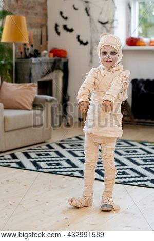 Little boy wrapped in bandage as mummy standing in front of camera in domestic room