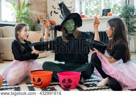 Young female in witch attire putting treats in hats of two adorable girls while sitting on the floor