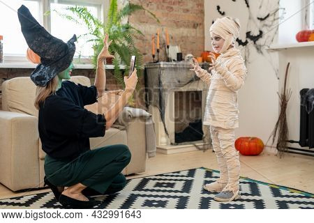 Female in witch costume taking photo of her little son in zombie attire in living-room