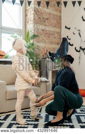 Young mother in witch costume wrapping her little son into zombie attire in domestic room
