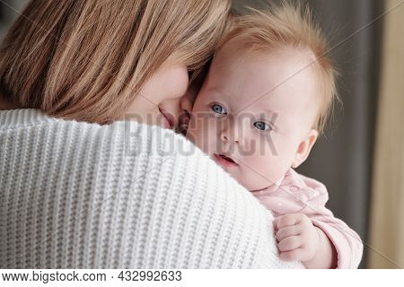 Face of adorable baby girl on hands of her happy young affectionate mother