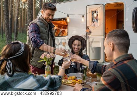 Happy friends clinking glasses of wine over served table while enjoying dinner by house on wheels