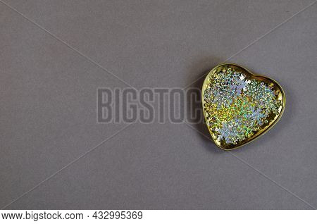 A Gold Metal Heart Filled With Multicolored Sequins On A Gray Background. Romance, Love. View From A