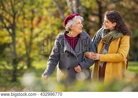 Young woman in park wearing winter clothing walking with old grandmother. Smiling lovely caregiver and senior lady walking in park during autumn and looking at each other with copy space.
