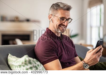 Smiling mature man with eyeglasses using smartphone at home. Handsome happy mid man with spectacles using cellphone while relaxing on couch. Successful businessman laughing while reading message.