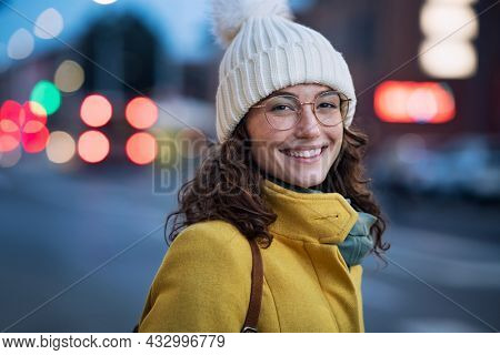 Portrait of happy young woman wearing warm hat with eyeglasses on city street and looking at camera. Beautiful student with cap and winter coat walking at urban road at dusk with copy space.