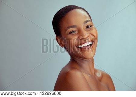 Happy beauty african woman looking at camera isolated on background with copy space. Cheerful mid woman smiling after skin treatment. Beautiful middle aged lady having fun after beauty therapy.