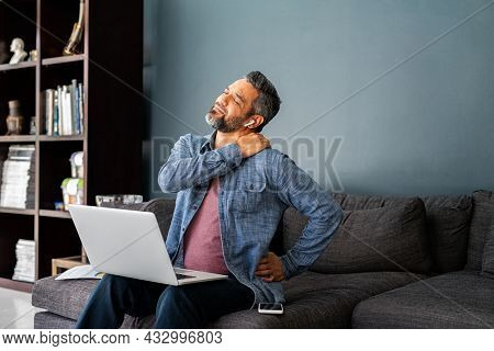 Mature indian man suffering from shoulder and back pain while sitting on couch and working from home on laptop. Stressed middle eastern businessman suffering from neck pain and stretching.