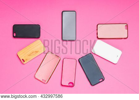 Choice Of Multicolored Plastic Back Covers For Mobile Phones On Pink Background With A Smart Phone O