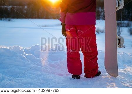 Snowboarder Holding A Snowboard On Top Of The Mountain And Looking Reflecting Into A Distance. Winte