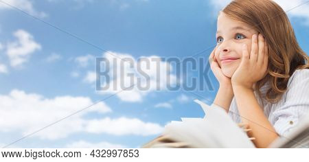 education and school concept - little student girl with book daydreaming over blue sky and clouds background