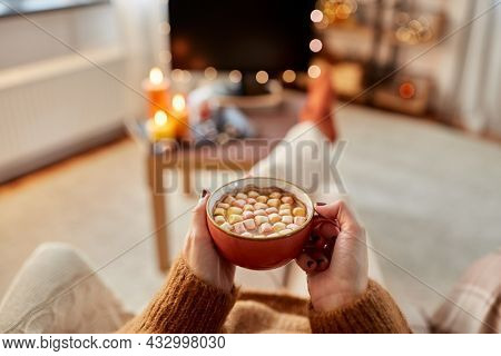 people and leisure concept - young woman watching tv and drinking hot chocolate with marshmallow with her feet on table at cozy home