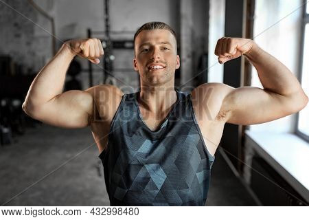sport, bodybuilding, fitness and power concept - happy smiling young man showing his bicep muscles in gym
