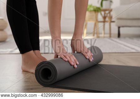 Woman Unrolling Yoga Mat At Home, Closeup