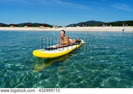 Relaxed Travel Woman In Swimsuit Sunbathing On Surfboard Enjoying Sup Surfing Extreme Sport